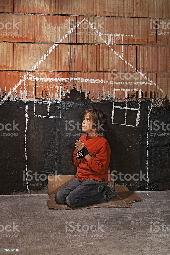 Poor homeless beggar boy praying for a shelter concept stock photo
