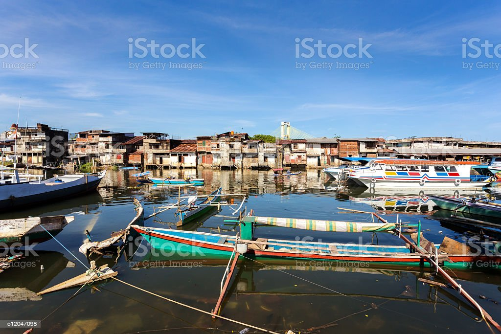 poor houses by the river in shantytown stock photo