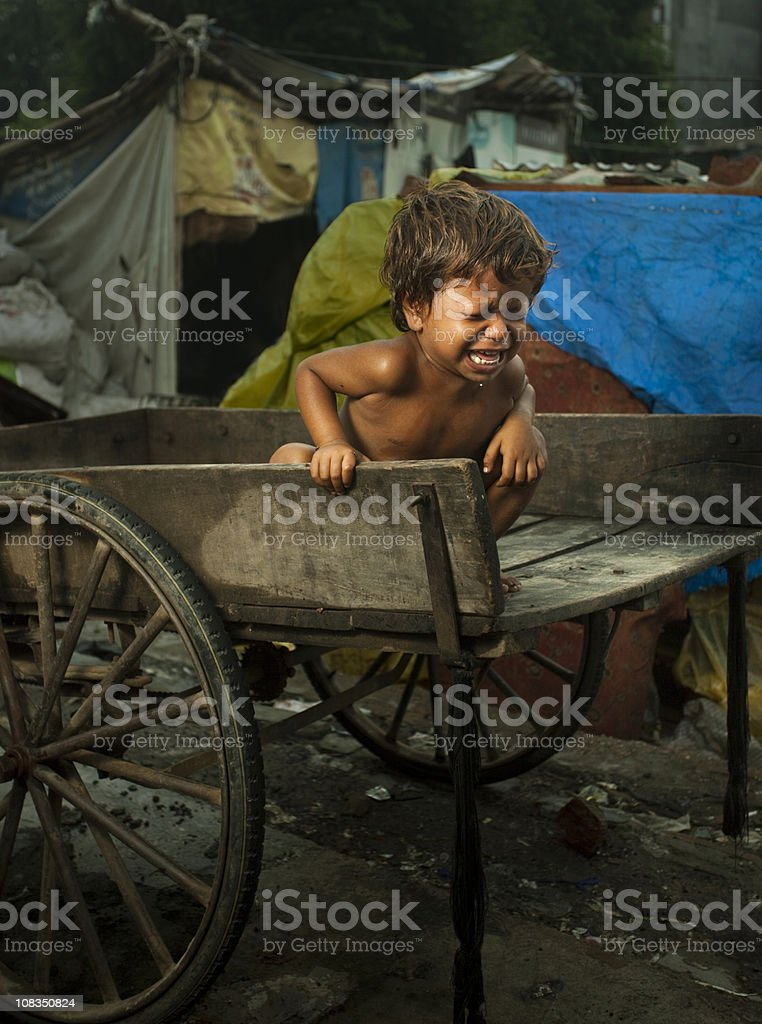 Poor, hungry child sitting on a cart and crying loudly royalty-free stock photo