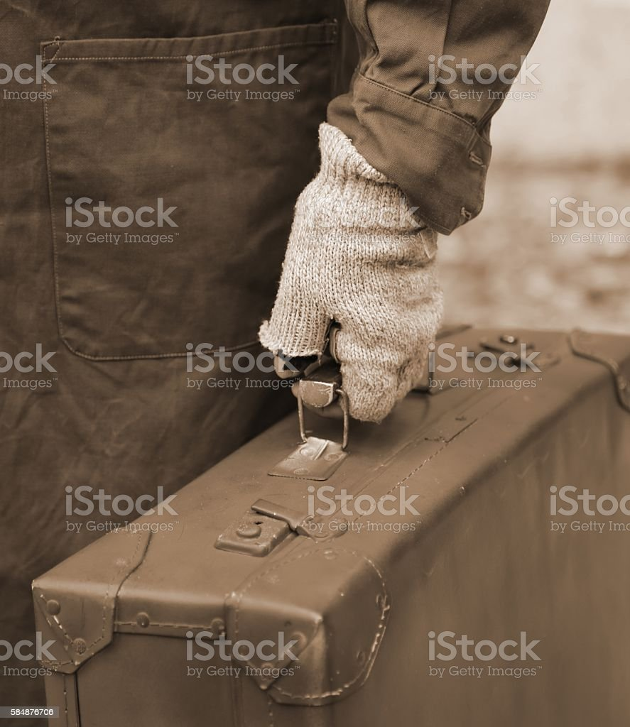 poor immigrant with old leather suitcase and the unstitched glov stock photo