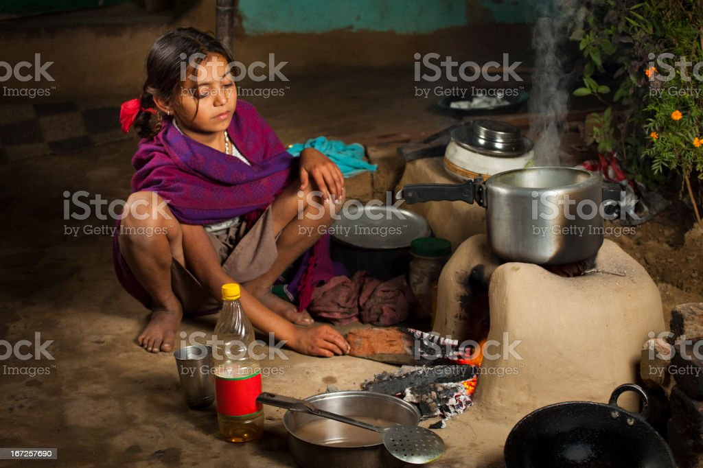 Poor, Indian girl cooking food on a clay stove royalty-free stock photo