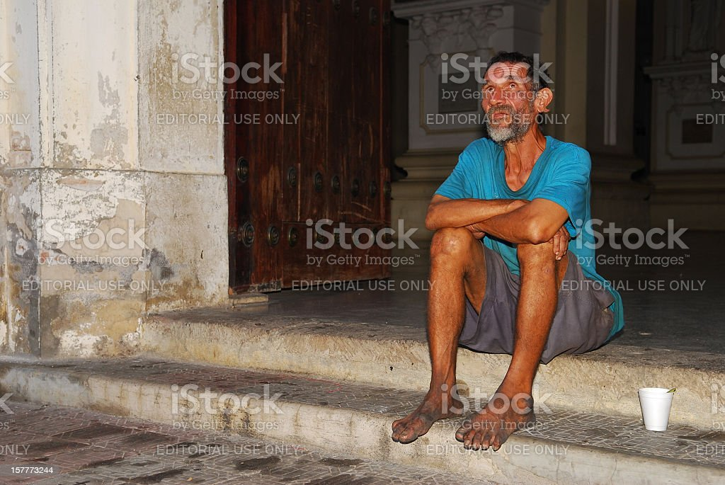 Poor man on church steps in Leon, Nicaragua stock photo