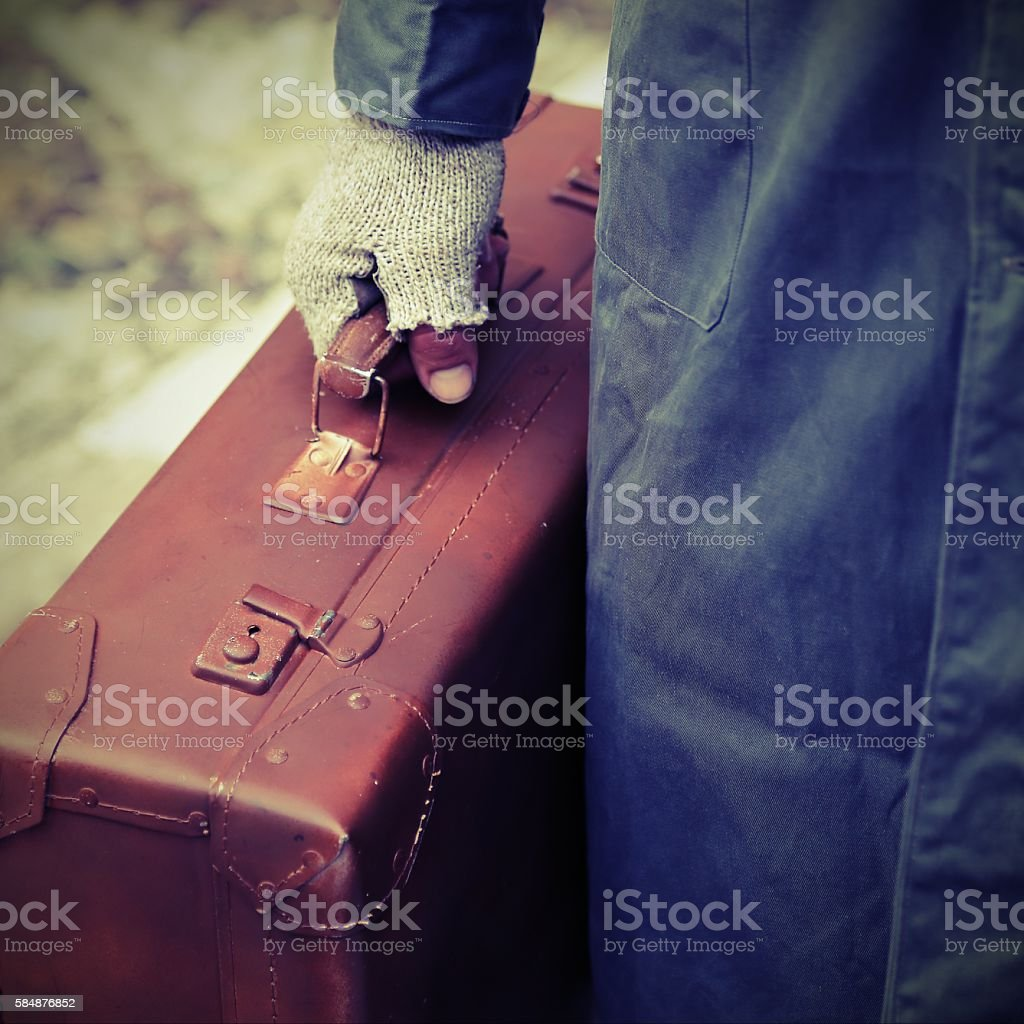 poor traveler with old worn leather suitcase stock photo