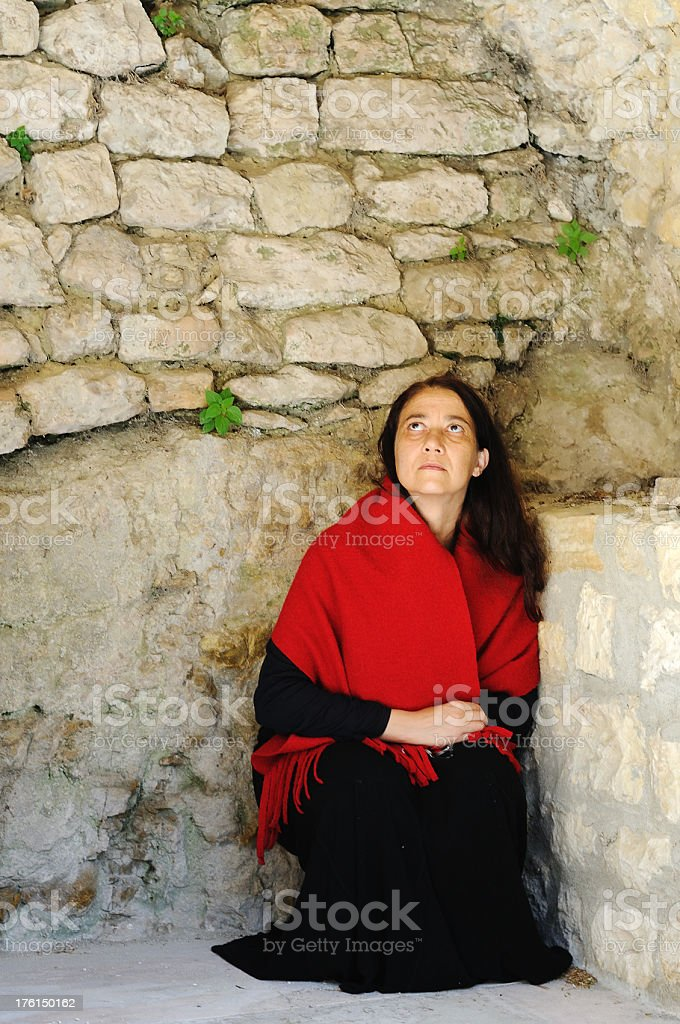 Poor woman looking up in stone corner stock photo