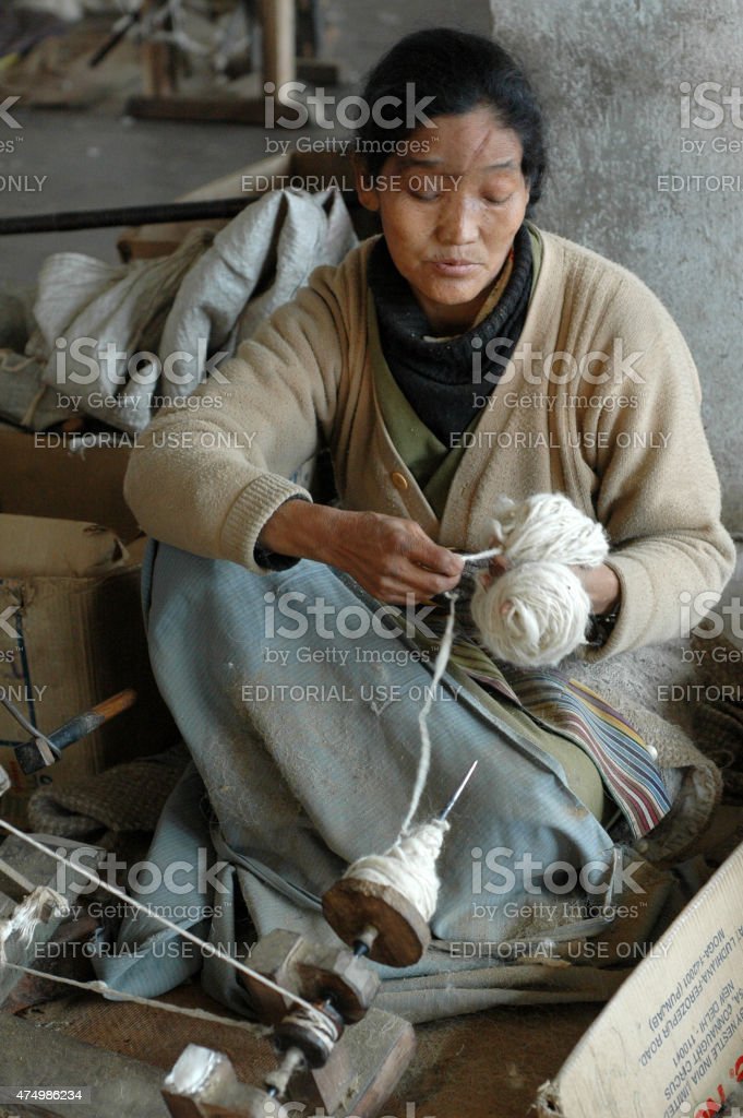 Poor Woman Spinning Yarn. Rug Industry in Asia. stock photo