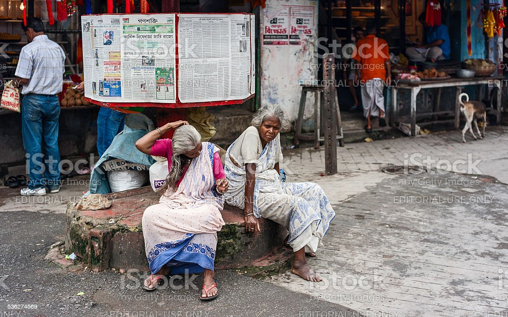 Poor women sit under free newspaper stand, Kolkata, India. stock photo