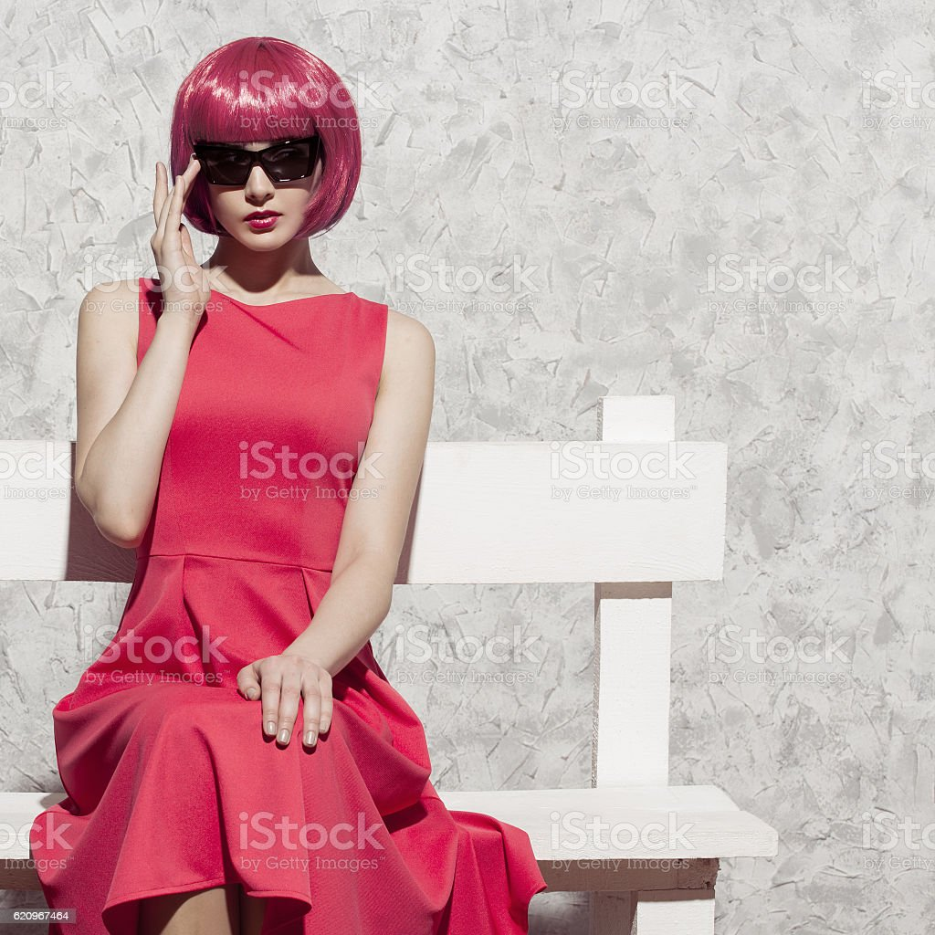 Pop art woman in sunglasses sitting on white bench. stock photo