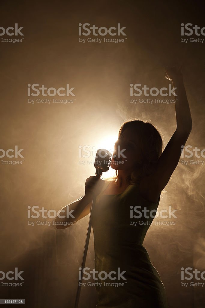 Pop idol backlit with microphone on the big stage stock photo