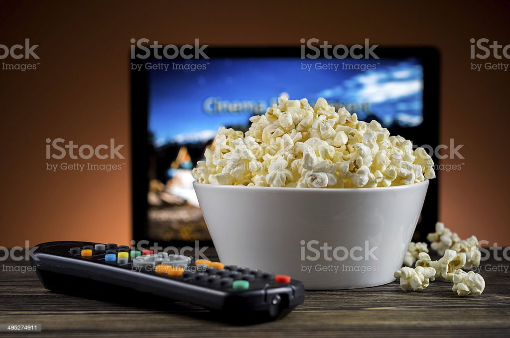 Popcorn and a remote control for the TV background stock photo