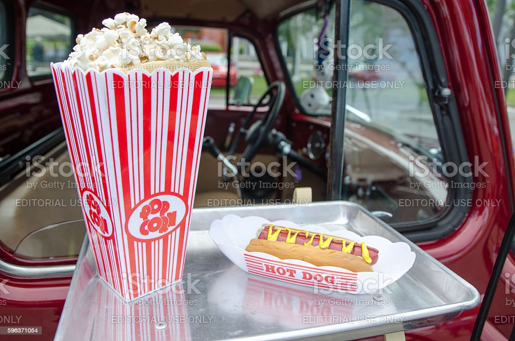 PopCorn and hot-dog in a tray hanging on car window stock photo