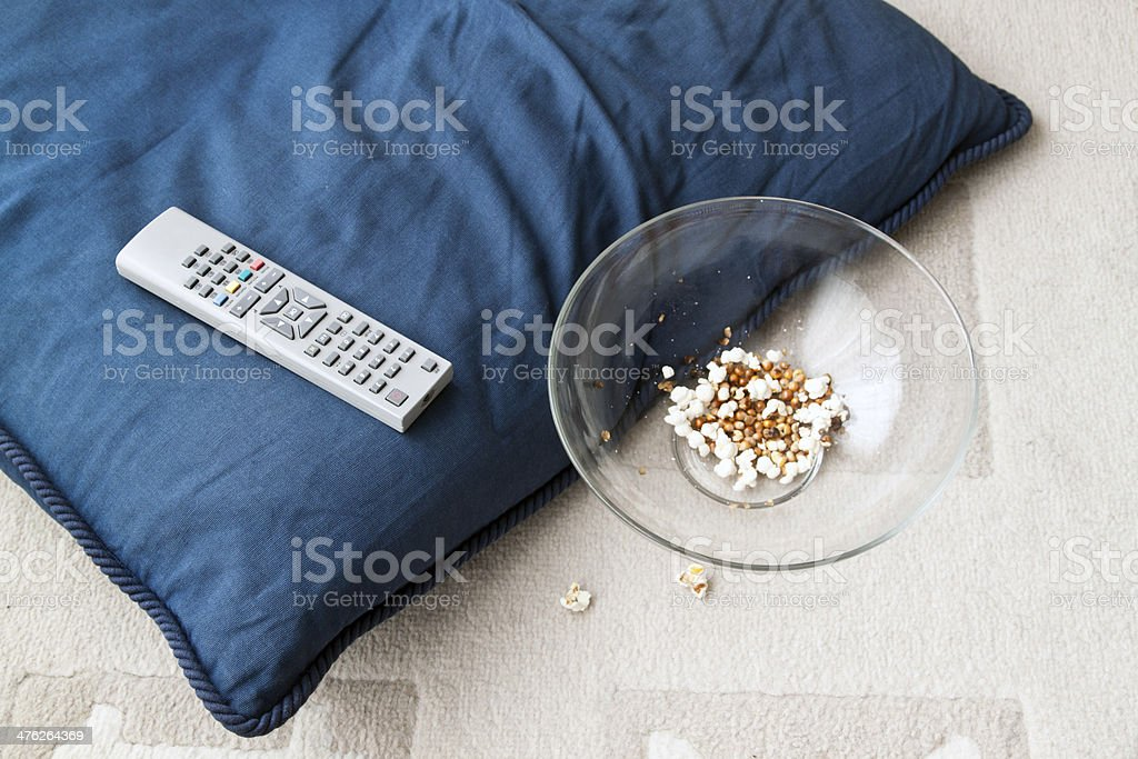 Popcorn bowl, remote control and a cushion royalty-free stock photo