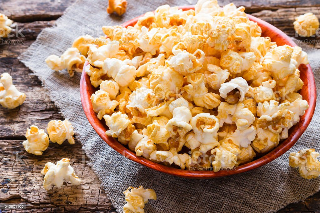 Popcorn in a bowl and scattered on a table close-up stock photo