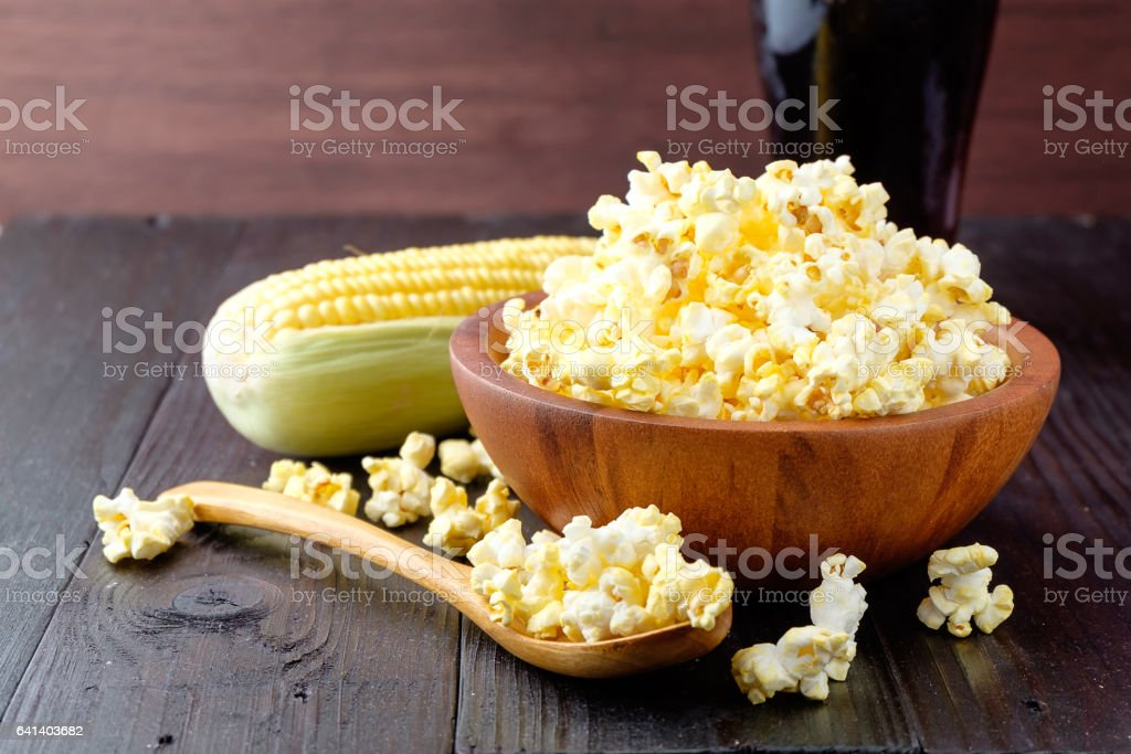 Popcorn in a bowl on wooden background. stock photo