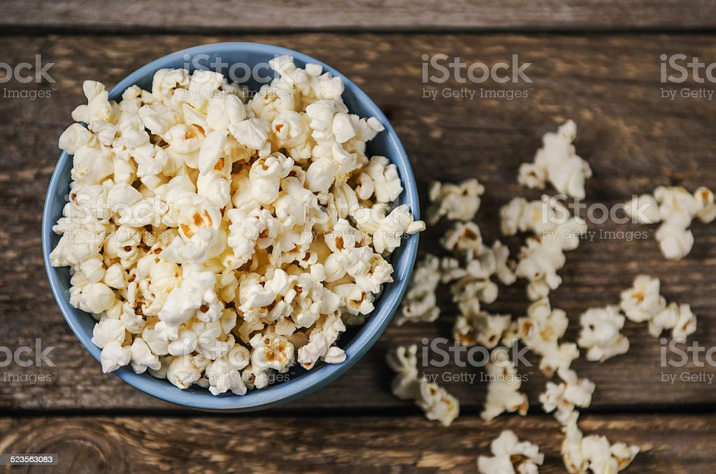 Popcorn in a bowl on wooden table stock photo