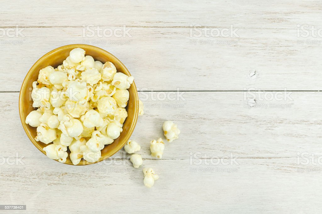 Popcorn in bowl on wood table. stock photo