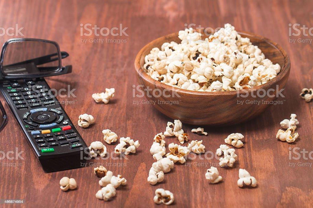 Popcorn, remote control and 3D glasses stock photo