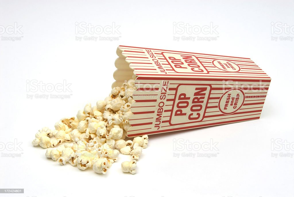 Popcorn spilling from red and white popcorn box-isolated on white stock photo