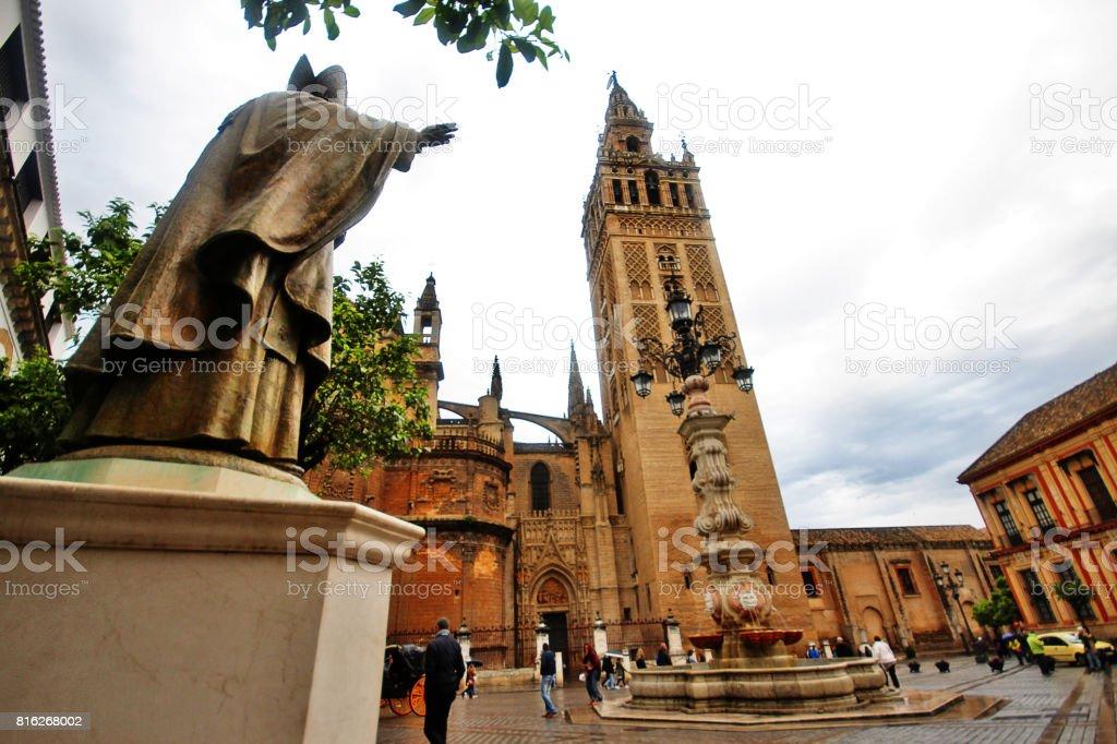 Pope John Paul II Statue (Juan Pablo II) and Giralda (Torre de la Giralda) at Plaza Virgen de Los Reyes, Seville (Sevilla), Andalusia, Southern Spain stock photo
