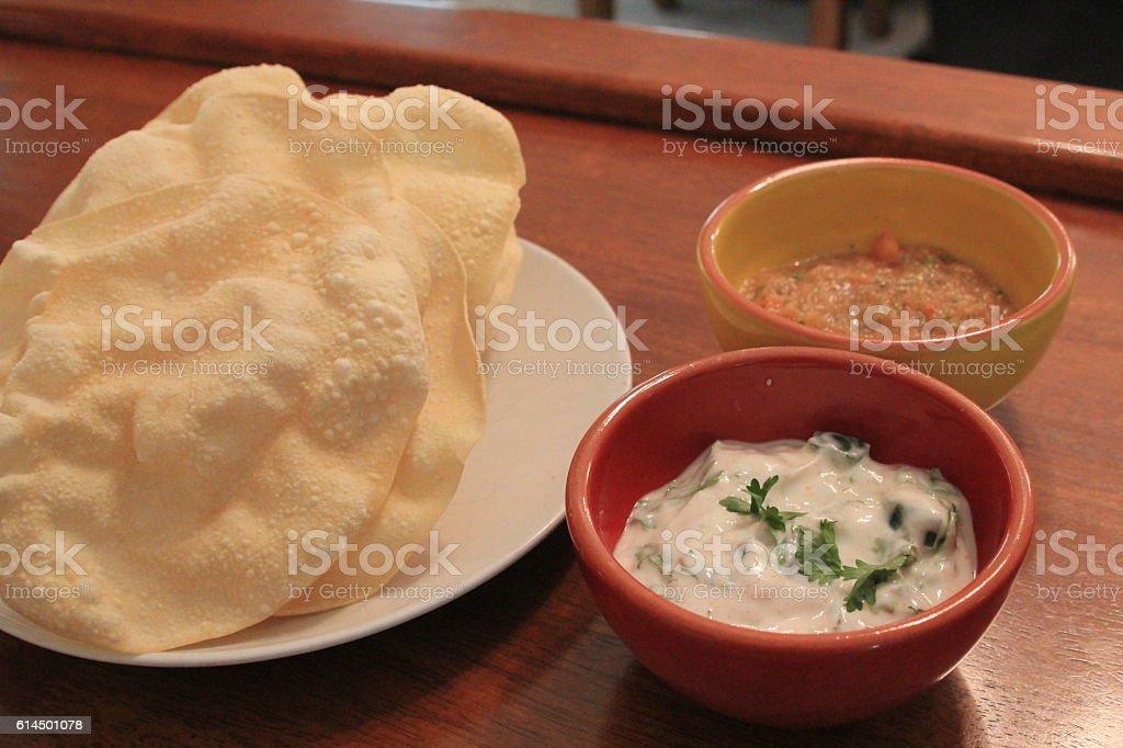 Poppadum with riati and spicy dip stock photo