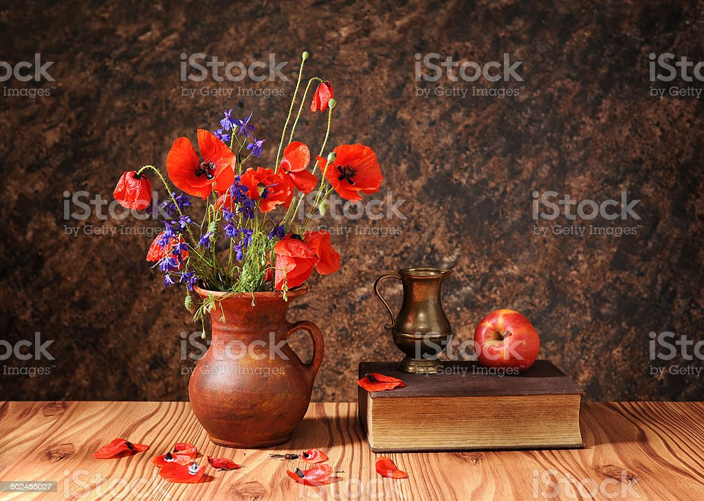 Poppy flower in a vase with an apple stock photo