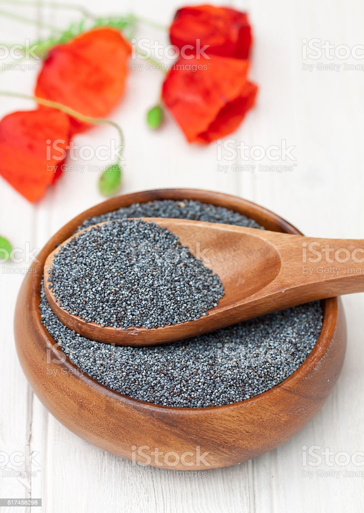 poppy  seeds in a wooden bowl on a table stock photo