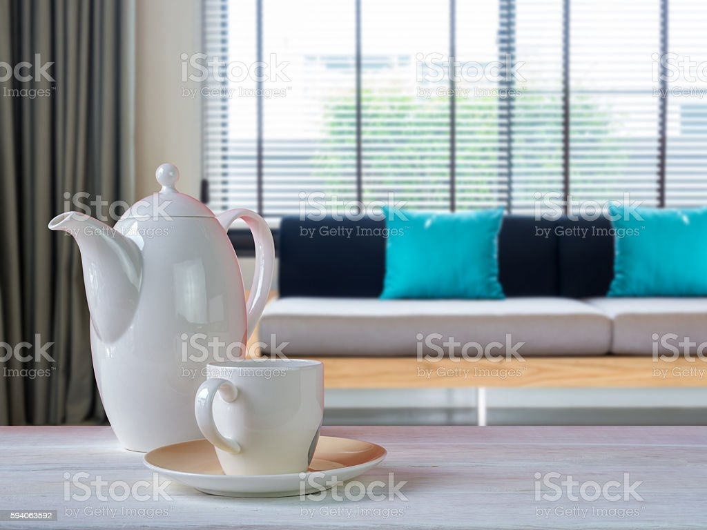 Porcelain coffee cup on wooden table with Living room  background stock photo