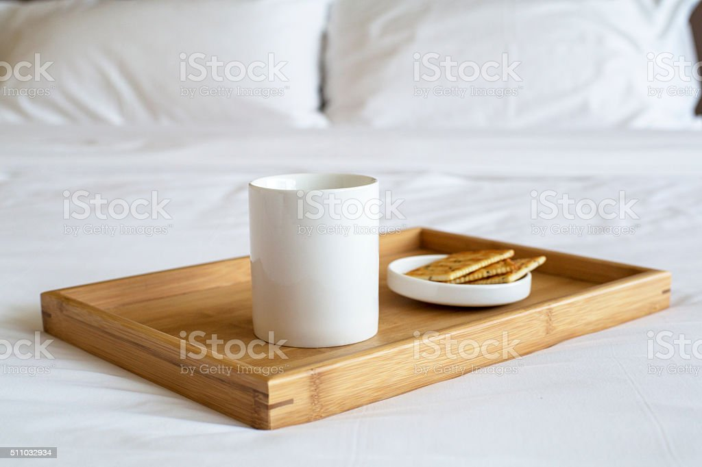 porcelain cup and biscuit on bed stock photo