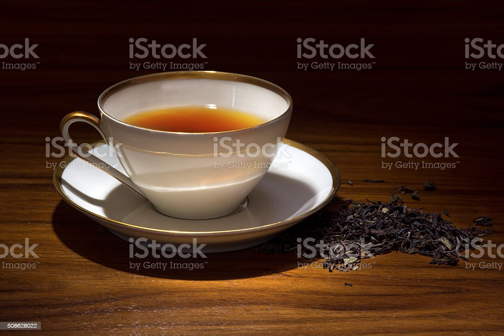 porcelain cup with tea on a wooden table stock photo