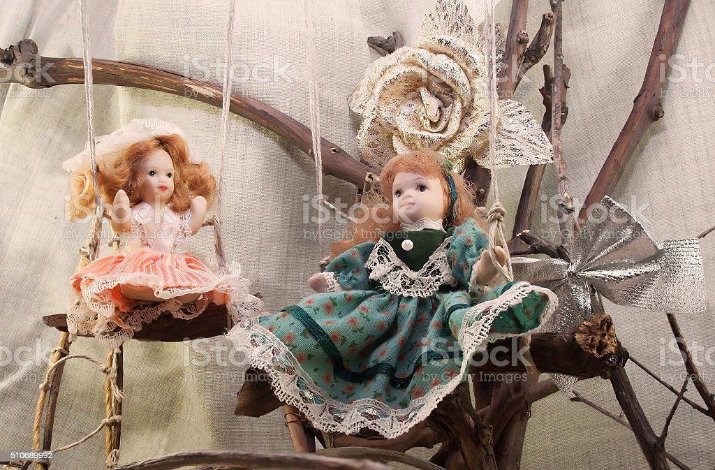 Porcelain dolls on swings photo. stock photo