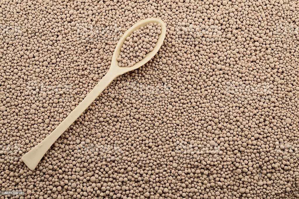 Porcelain laboratory spoon on mineral fertilizers stock photo
