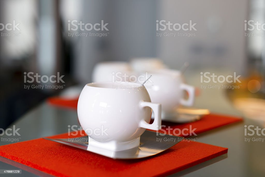 Porcelain modern cups with stainless steel saucers on felt coasters royalty-free stock photo