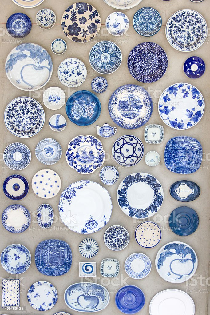 Porcelain plates placed on the cement floor for background. stock photo