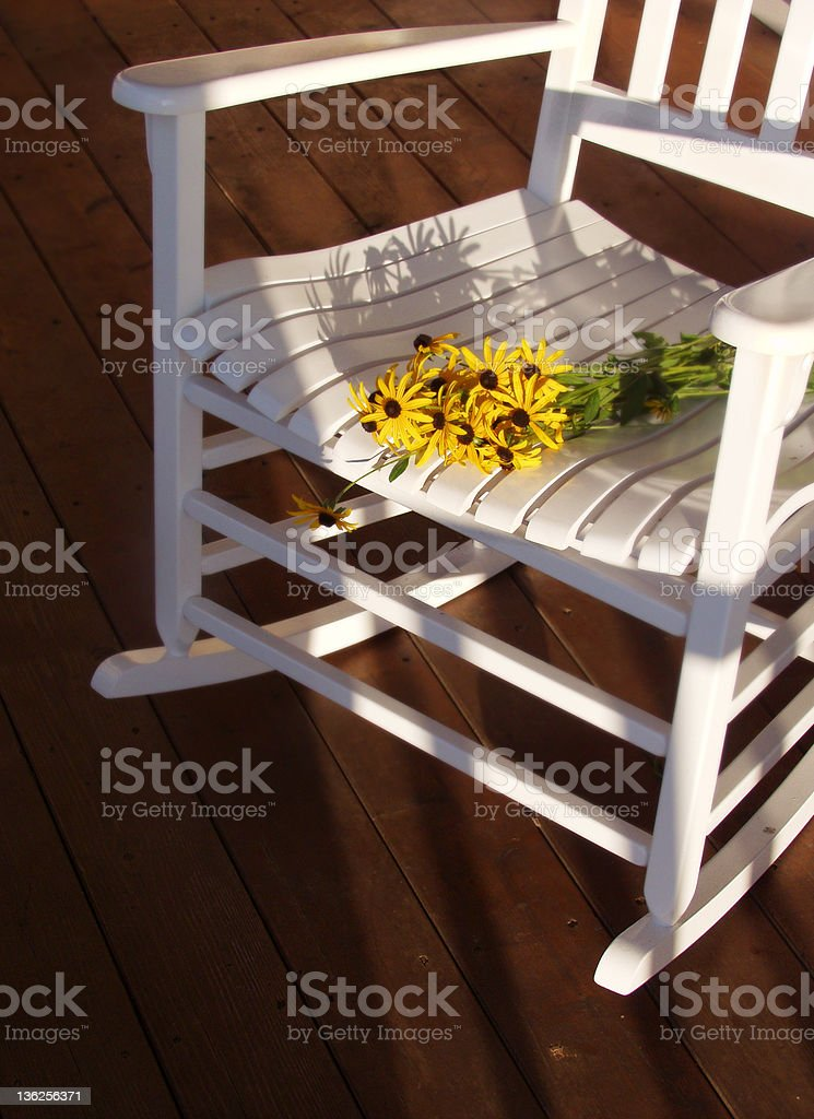 porch rocker and flowers stock photo