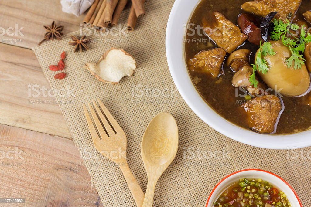 Pork and egg stewed in the gravy on wooden table royalty-free stock photo