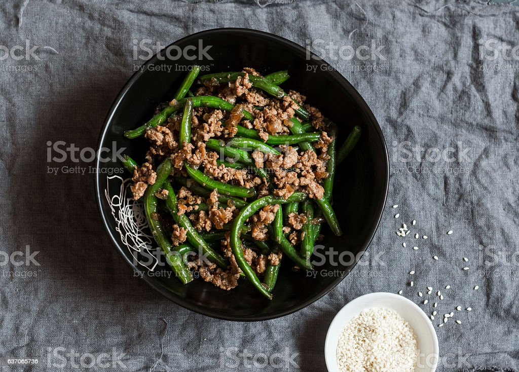 Pork and green beans stir fry on a dark table stock photo