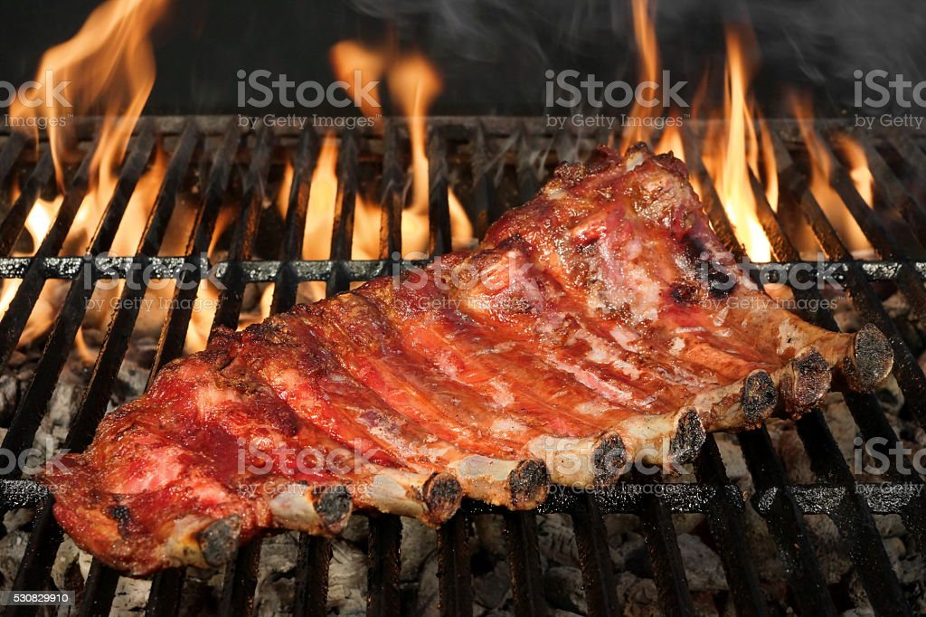 Pork Baby Back Or Spareribs On BBQ Grill With Flames stock photo