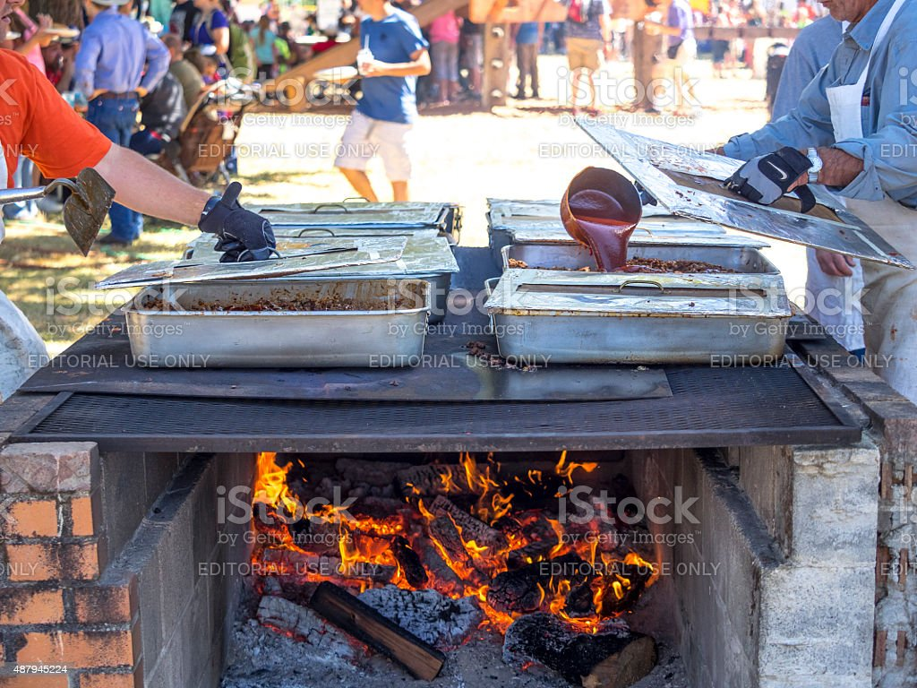 BBQ Pork Being Cooked for Sandwiches Over Wood Fire stock photo