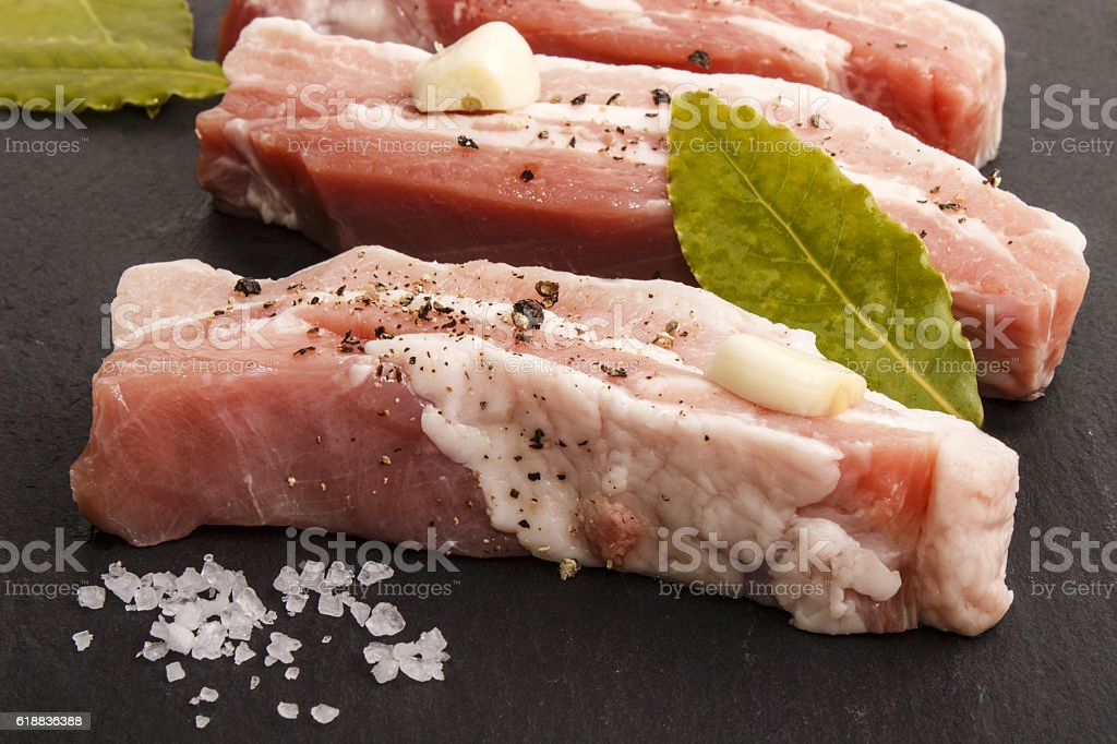 pork belly stripes on slate with spice and bay leaf stock photo