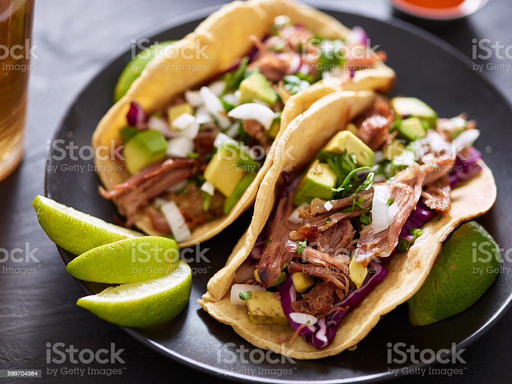 pork carnita tacos close up with lime wedges stock photo