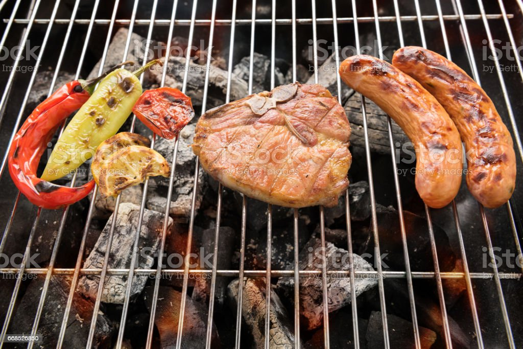 Pork chop steak and vegetable with sausage on a flaming BBQ grill stock photo