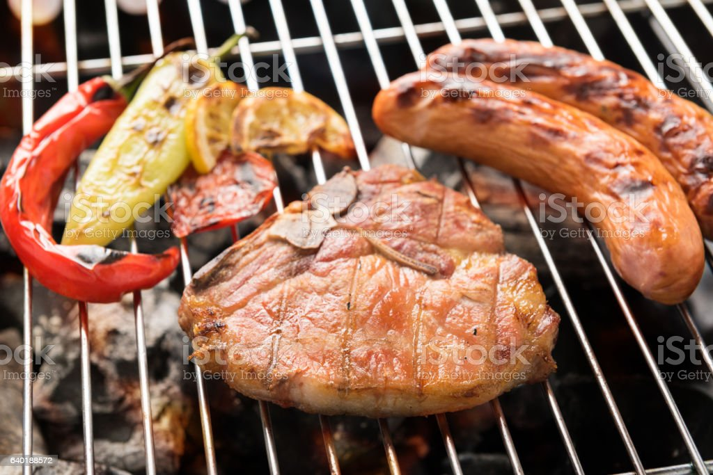 Pork chop steak and vegetable with sausage on BBQ gril. stock photo