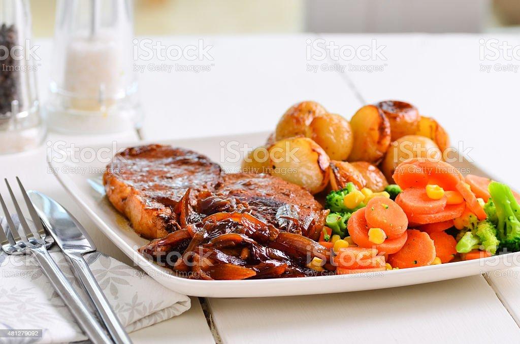 Pork chop Sunday lunch with onion gravy. stock photo