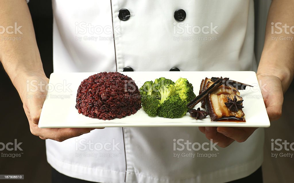 Pork Chop with brown rice on professional hand chefs. royalty-free stock photo