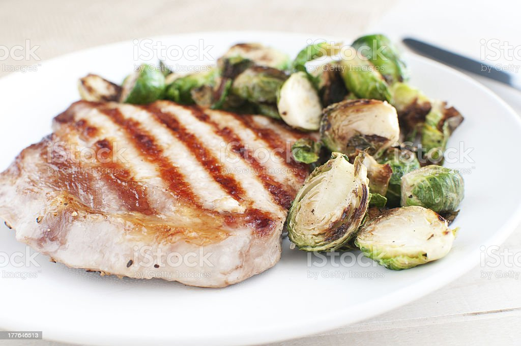 Pork chop with brussels sprouts royalty-free stock photo