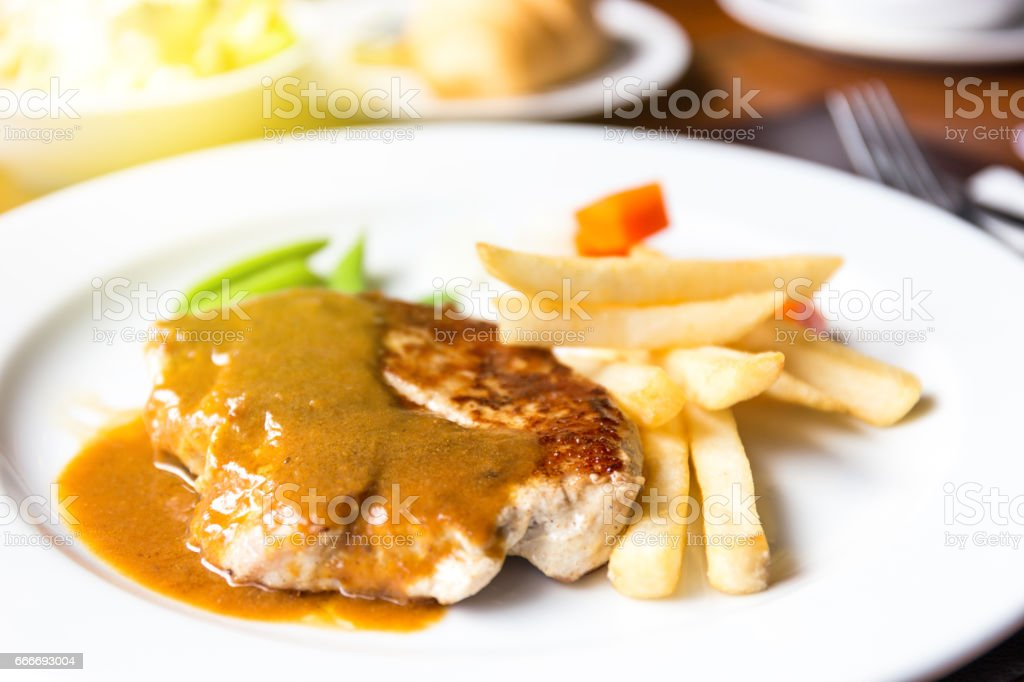 pork chop with dilicious sauce and french fries stock photo