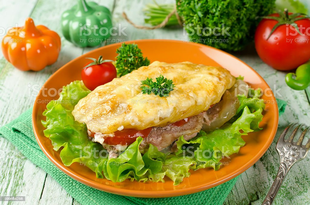 Pork chop with tomatoes, potatoes and cheese stock photo
