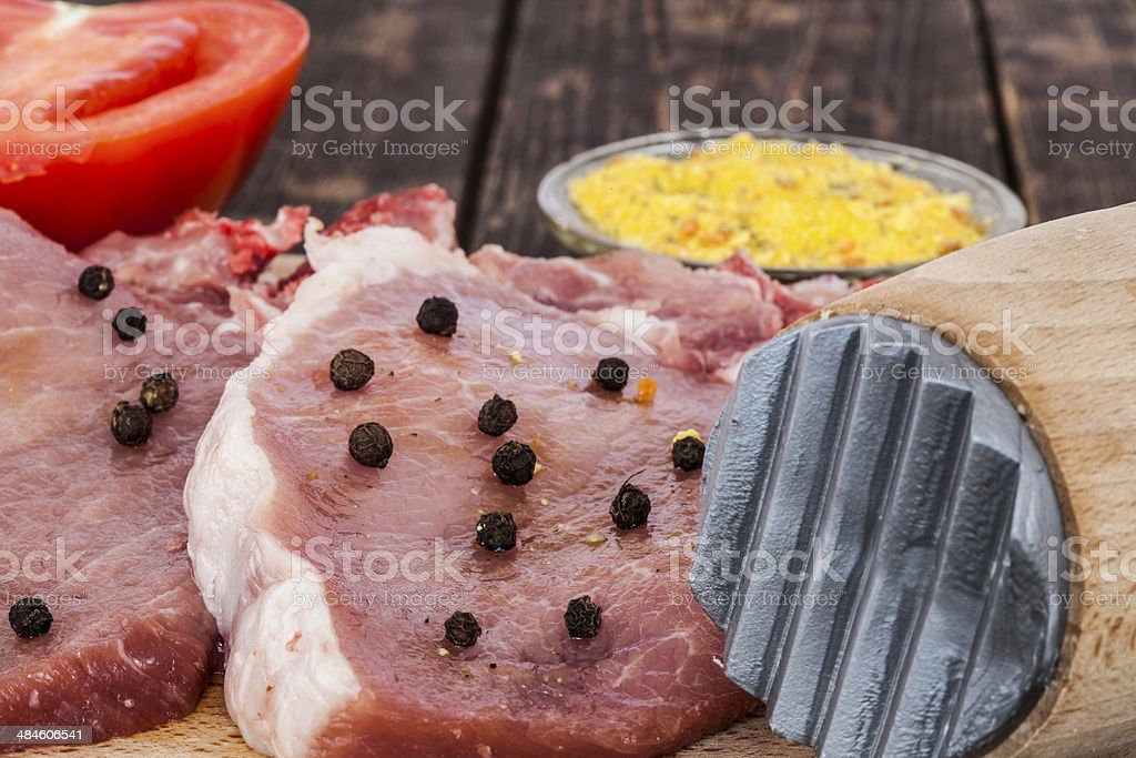 Pork chops and a meat hammer closeup royalty-free stock photo