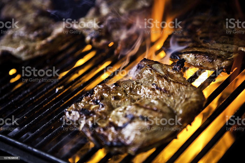 Pork chops cooking on a grill over flames stock photo