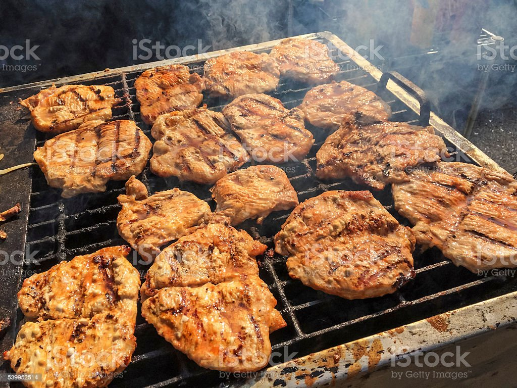 Pork chops cooking on an outside grill stock photo