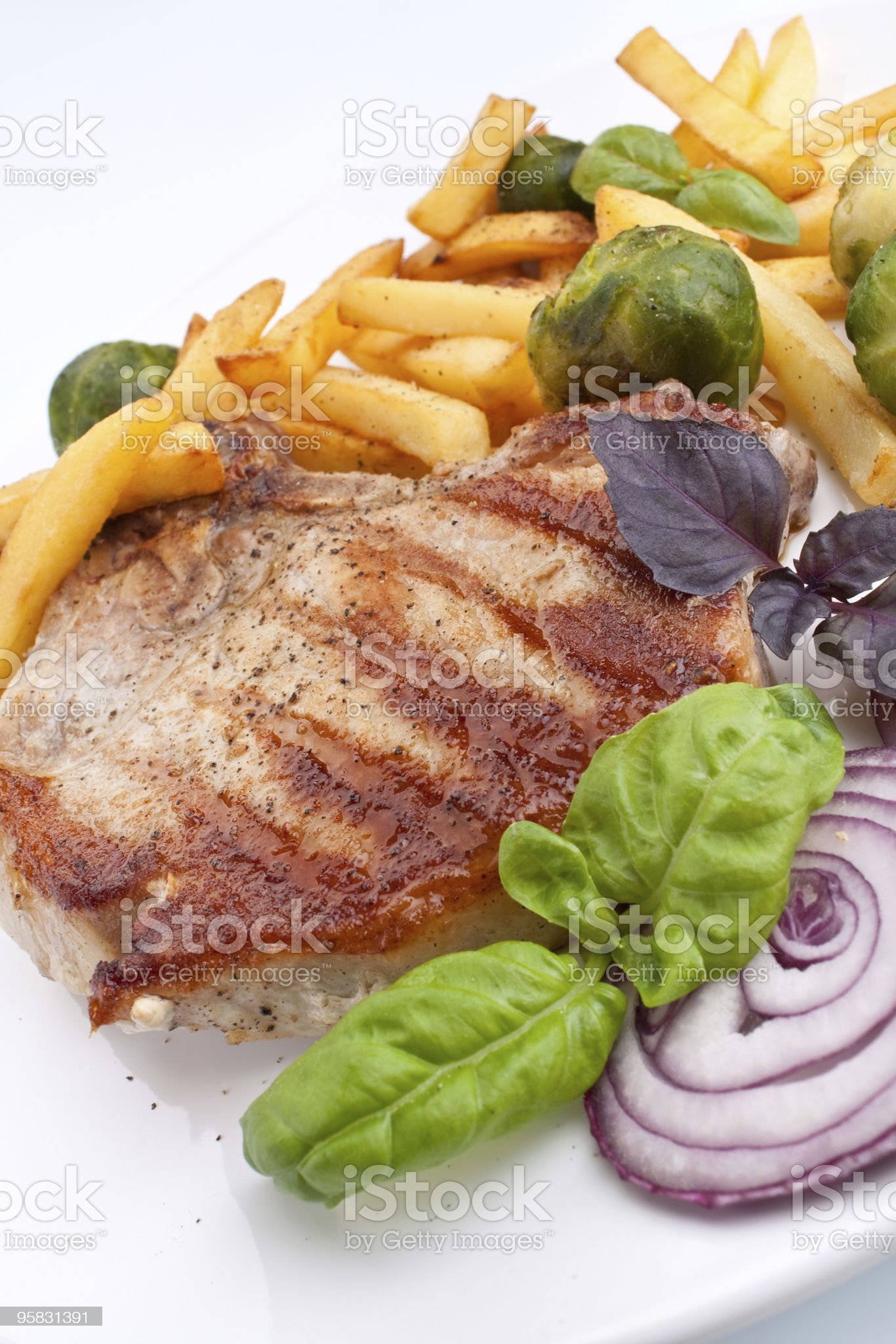 pork chops with fries and brussels sprouts royalty-free stock photo